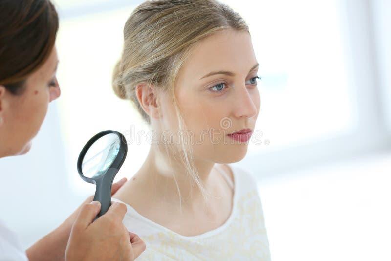Jonge vrouw bij dermathologist stock foto