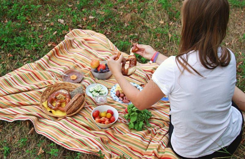 Jonge vrouw bij een picknick op een weide stock afbeeldingen