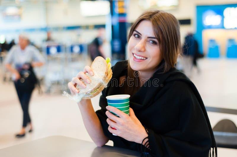 Jonge vrouw bij een restaurant in internationale luchthaven stock afbeeldingen