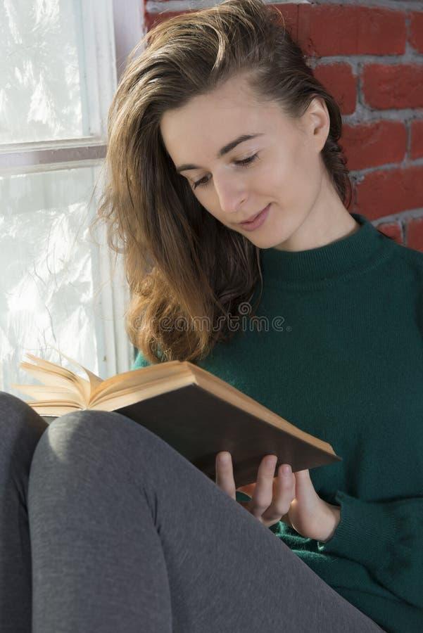 Jonge vrouw bij het de wintervenster royalty-vrije stock fotografie