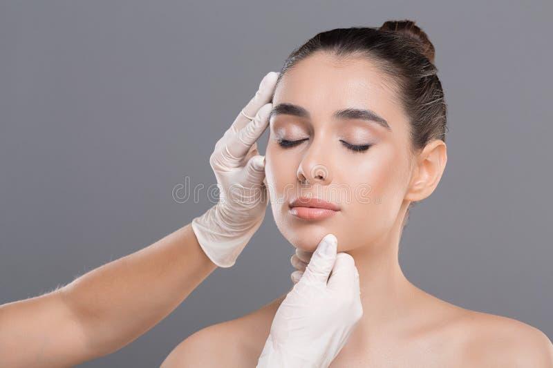 Jonge vrouw bij het overleg bij schoonheidsspecialist, grijze achtergrond stock foto's