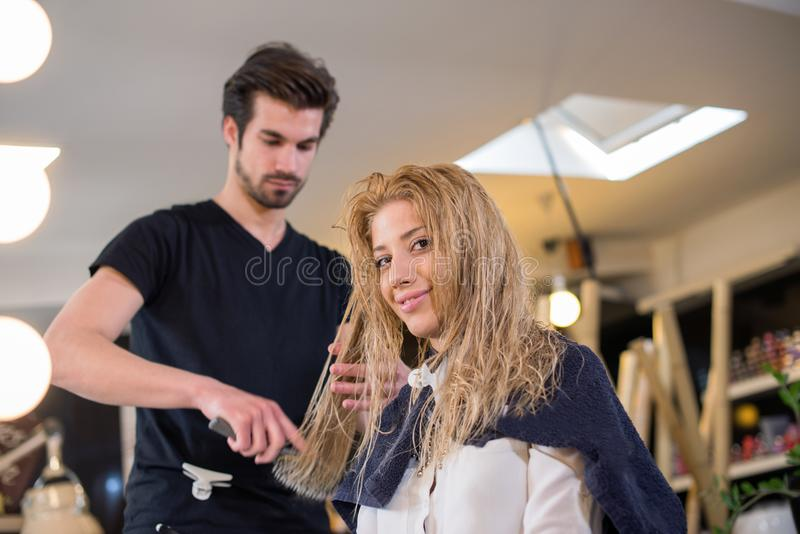 Jonge vrouw bij kapper, die een verandering in haar blik aanbrengen stock fotografie