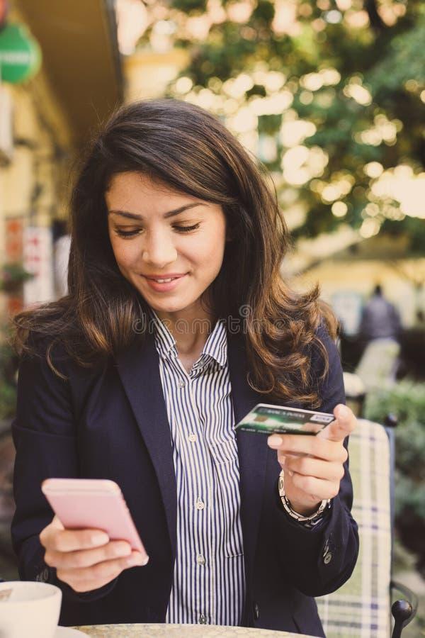 Jonge vrouw bij koffie die slimme telefoon met behulp van aan controlecreditcard stock afbeelding