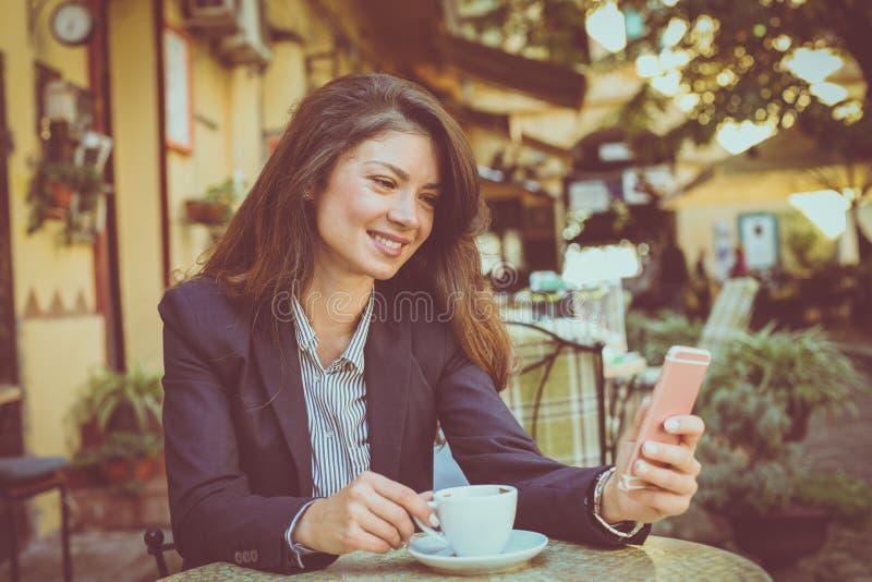 Jonge vrouw bij koffiepauze die slimme telefoon met behulp van stock foto