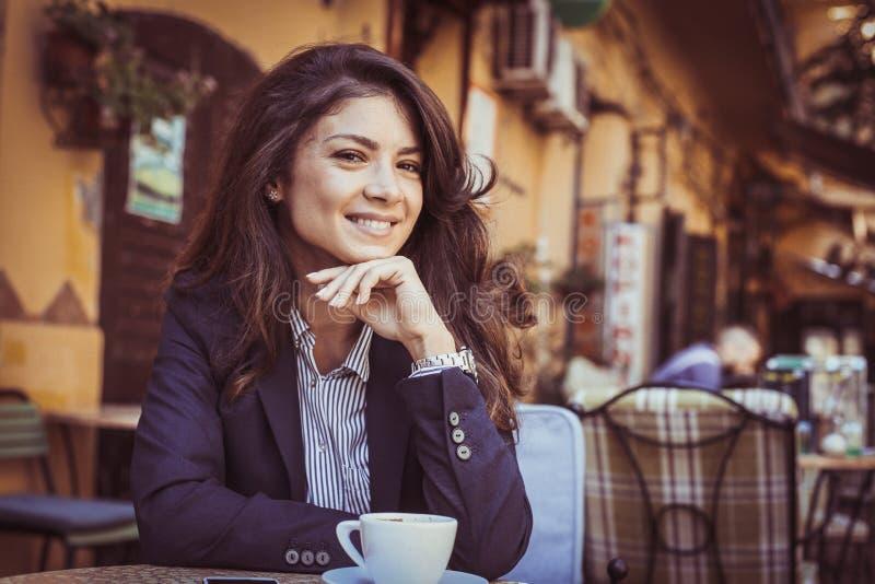 Jonge vrouw bij koffiepauze het bekijken camera stock fotografie