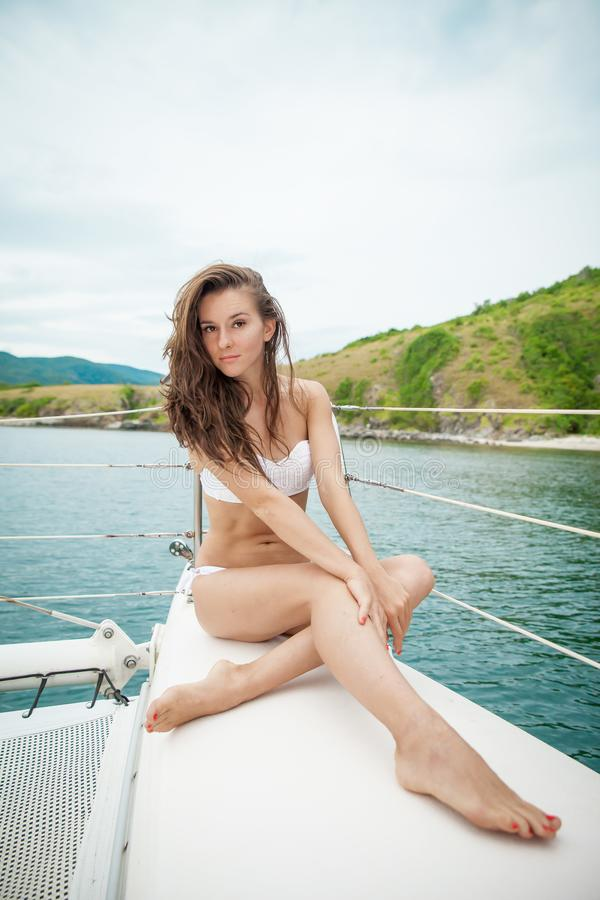 Jonge vrouw in bikinizitting op cruiseschip terwijl het reizen in de oceaan stock fotografie