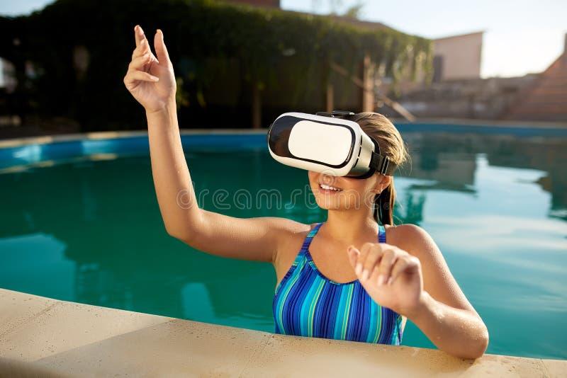 Jonge vrouw in bikinizwempak die waterdichte virtuele werkelijkheidsglazen in zwembad speelspel gebruiken Blondemeisje met stock afbeeldingen