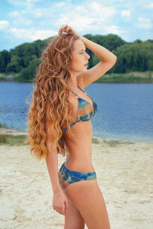 Jonge vrouw in blauwe bikini op rivierstrand royalty-vrije stock afbeeldingen