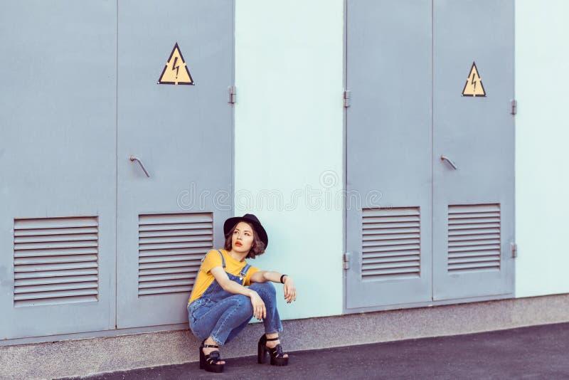 Jonge vrouw in blauwe denimoverall en gele t-shirt met het zwarte hoed sensuele kijken omhoog terwijl het stellen dichtbij de ind royalty-vrije stock foto's
