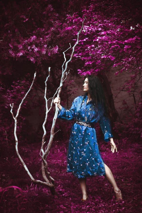 Jonge vrouw in blauwe kimono staat in infraroodtuin met grote witte tak stock afbeeldingen