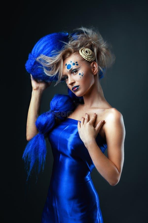 Jonge vrouw in blauwe pruik stock afbeelding