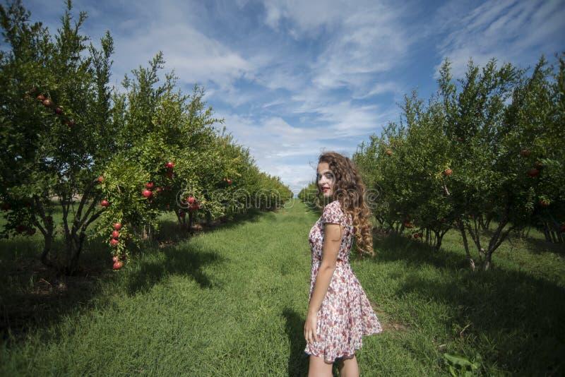 Jonge vrouw in bloemen lange kledings amongpomegranate bomen stock afbeeldingen