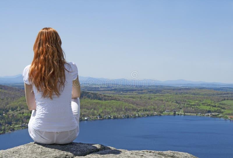 Jonge vrouw bovenop een berg stock fotografie