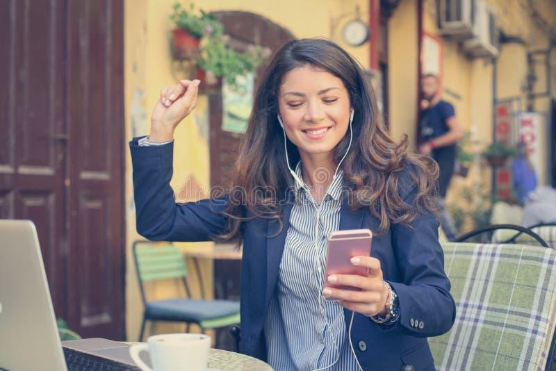 Jonge vrouw buiten, gebruikend slimme telefoon aan het luisteren muziek stock afbeelding