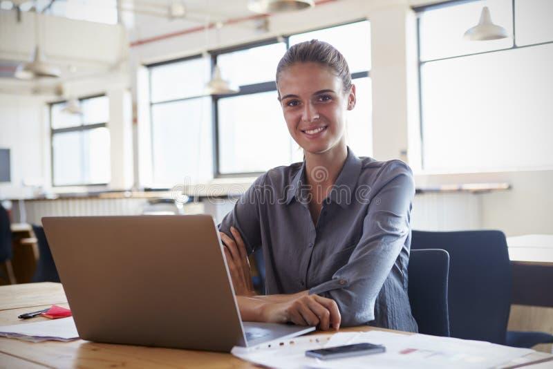 Jonge vrouw in bureau die laptop met behulp van, die aan camera glimlachen royalty-vrije stock afbeelding