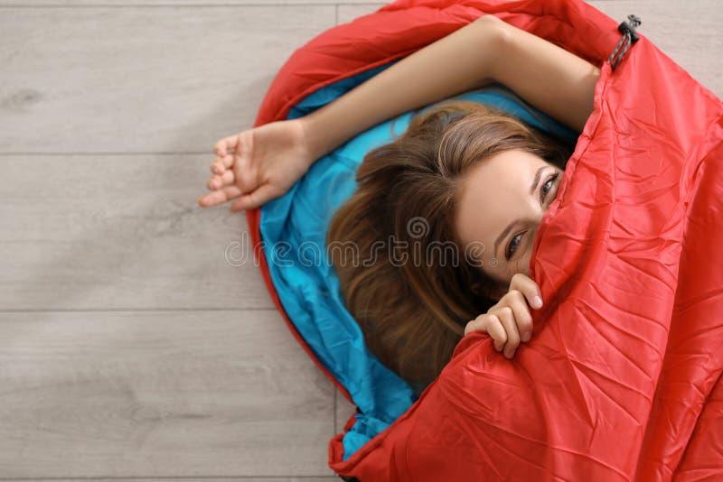 Jonge vrouw in comfortabele slaapzak op vloer stock afbeeldingen