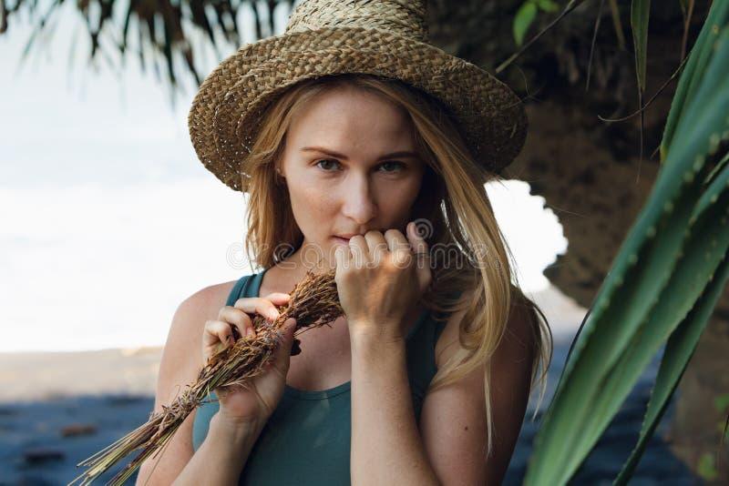 Jonge vrouw in de greepboeket van de strohoed van droge wildflowers royalty-vrije stock foto's