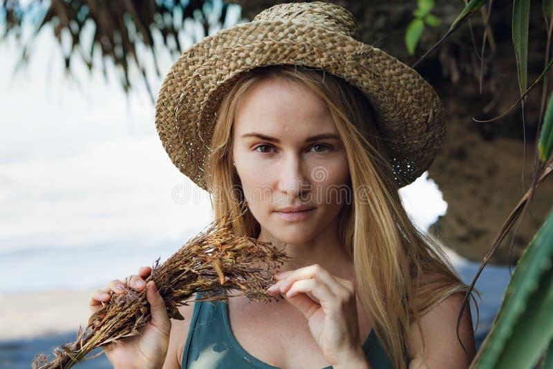 Jonge vrouw in de greepboeket van de strohoed van droge wildflowers royalty-vrije stock afbeelding