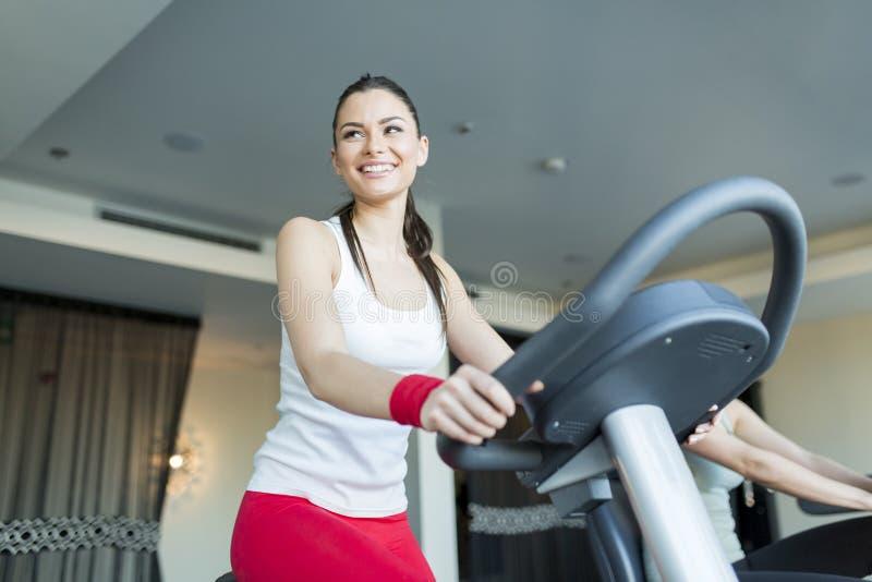 Jonge vrouw in de gymnastiek stock afbeeldingen