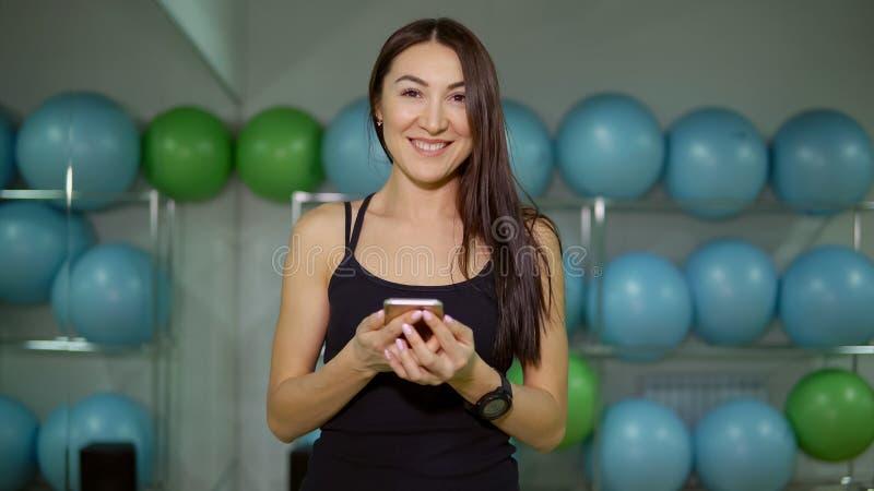 Jonge vrouw in de gymnastiek die aan muziek op de achtergrond van gymnastiek- ballen luisteren royalty-vrije stock foto's