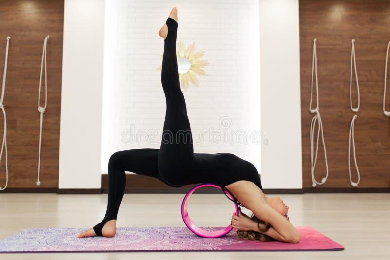 Jonge vrouw in de oefeningen van een sportkledingsyoga met een yogawiel in de gymnastiek Het uitrekken zich en wellnesslevensstij stock fotografie