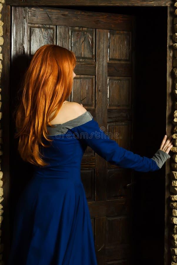 Jonge vrouw in de open deur van de renaissancekleding royalty-vrije stock afbeeldingen