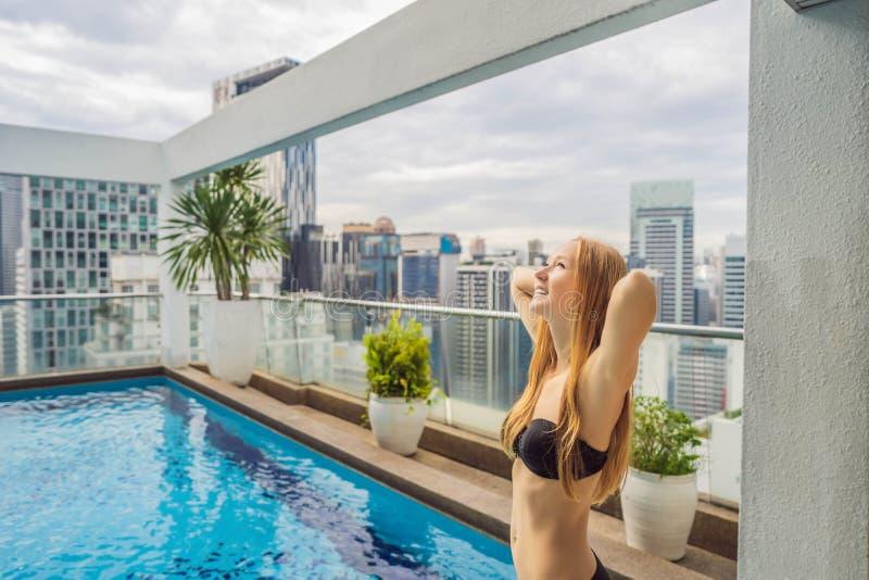 Jonge vrouw in de pool onder de wolkenkrabbers en de grote stad Ontspan in de grote stad Rust van spanning royalty-vrije stock foto