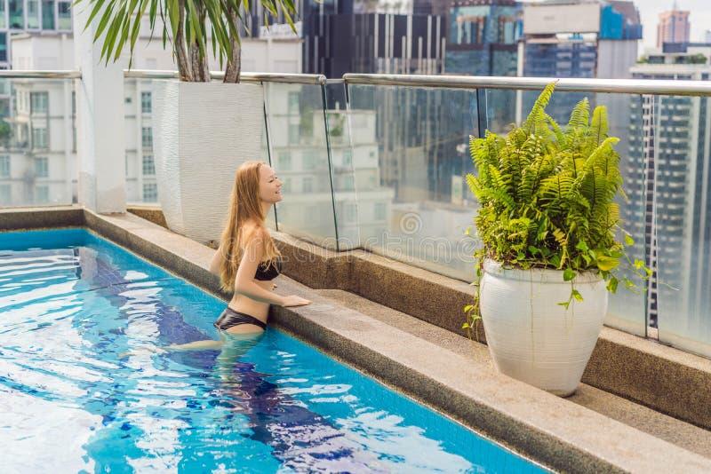 Jonge vrouw in de pool onder de wolkenkrabbers en de grote stad Ontspan in de grote stad Rust van spanning royalty-vrije stock afbeeldingen