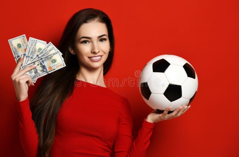 Jonge vrouw in de rode eenvormige bal van het greepvoetbal en dollargeld voor sporten die het vieren wedden stock afbeeldingen