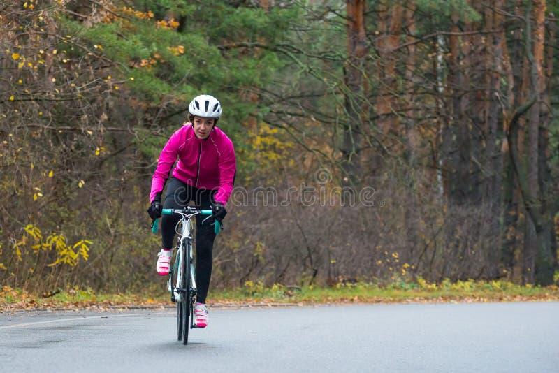Jonge Vrouw in de Roze Fiets van de Jasje Berijdende Weg in het Park in Koud Autumn Day Gezonde Levensstijl royalty-vrije stock foto's