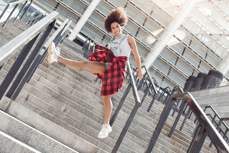 Jonge vrouw in de stadsstraat die op tredenbeen die omhoog springen vrolijke camera kijken royalty-vrije stock afbeeldingen