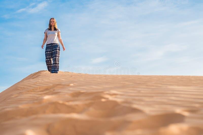 Jonge vrouw in de zandige woestijn van rad bij zonsondergang stock fotografie