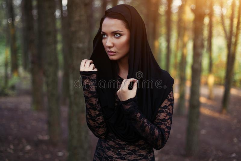 Jonge vrouw in de zwarte blouse en kap in het de herfstbos royalty-vrije stock foto