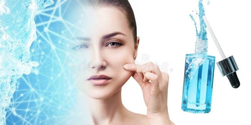 Jonge vrouw dichtbij blauwe kosmetische fles onder blauwe waterplons stock foto