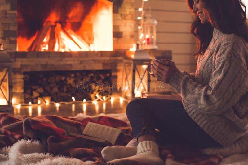 Jonge vrouw dichtbij de kop van de het conceptenholding van de open haard thuis winter stock fotografie