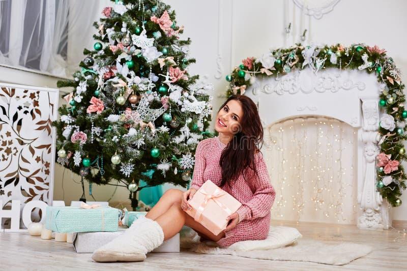 Jonge vrouw dichtbij een de giftdoos van de Kerstboomholding stock afbeeldingen