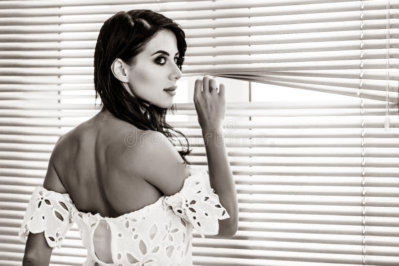Jonge vrouw dichtbij het venster royalty-vrije stock foto's