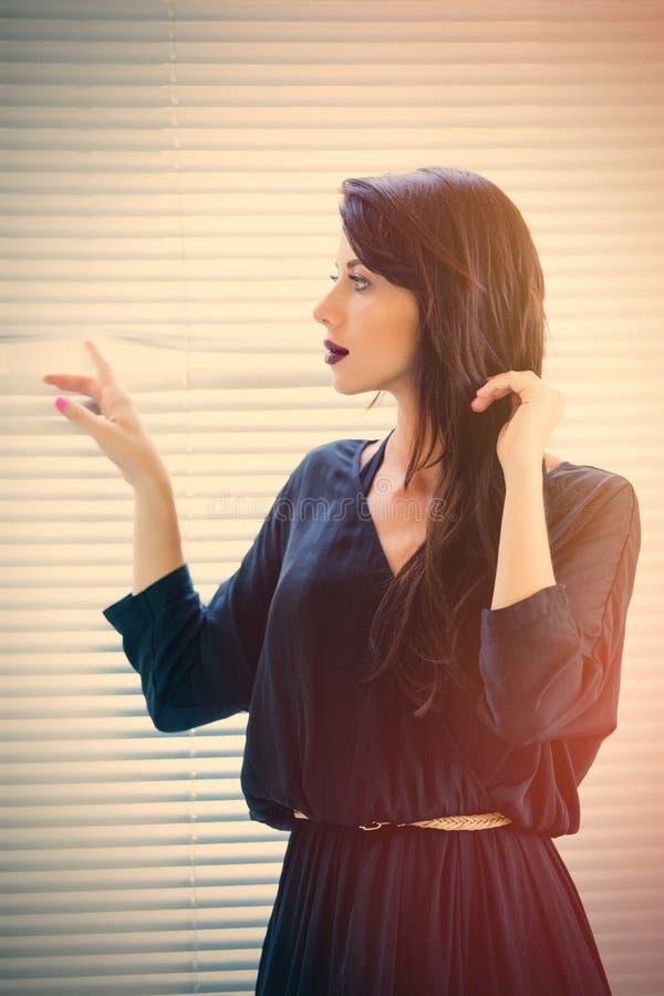 Jonge vrouw dichtbij het venster stock foto's