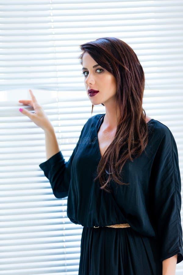 Jonge vrouw dichtbij het venster royalty-vrije stock fotografie