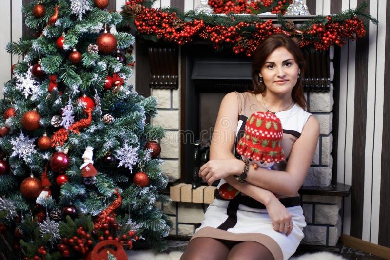 Jonge vrouw dichtbij Kerstboom en open haard stock afbeelding