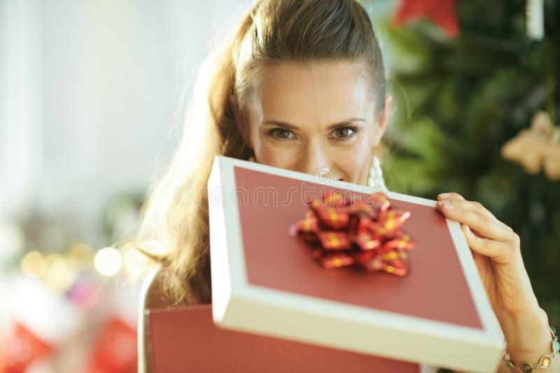 Jonge vrouw dichtbij Kerstboom het openen Kerstmis huidige doos stock afbeelding