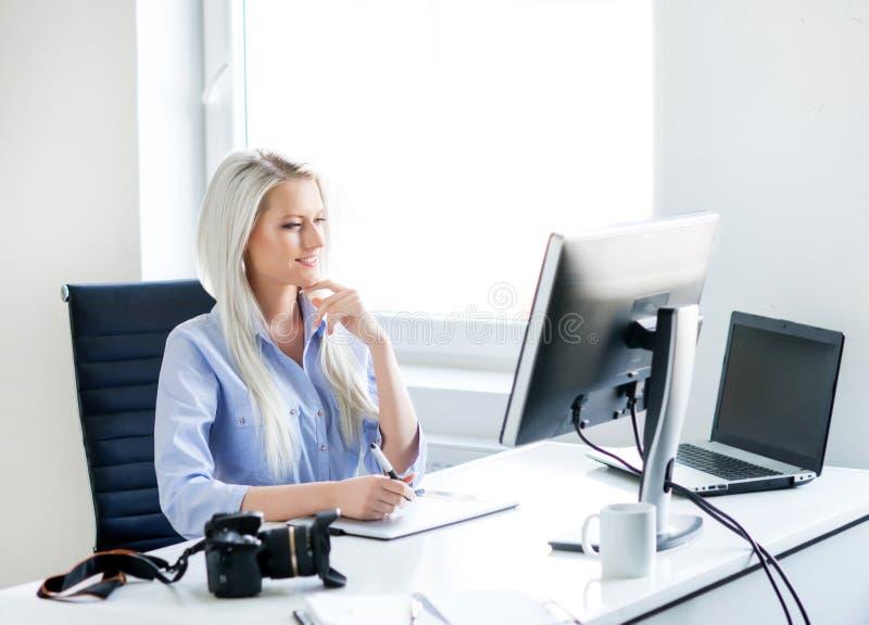 Jonge vrouw die aan de computer in het bureau werken royalty-vrije stock foto's