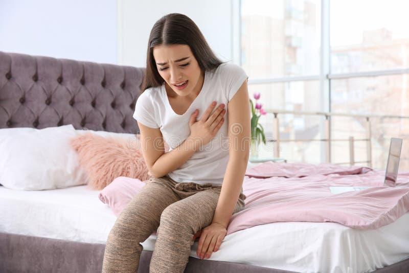 Jonge vrouw die aan hartaanval op bed lijden stock afbeeldingen