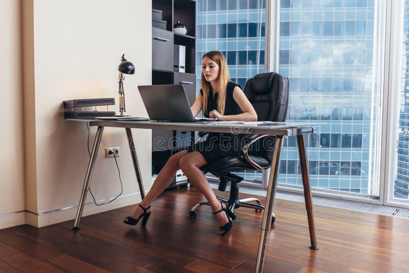 Jonge vrouw die aan laptop werken die financiële gegevens en statistieken van het bedrijf bestuderen royalty-vrije stock foto's