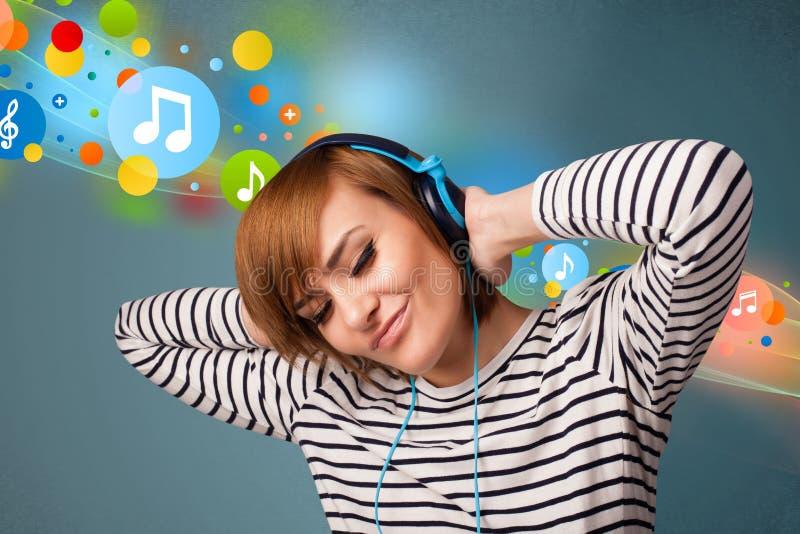 Jonge vrouw die aan muziek met hoofdtelefoons luistert royalty-vrije stock foto