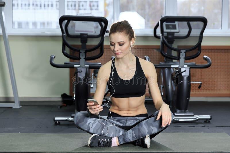 Jonge vrouw die aan muziek met oortelefoons in de gymnastiek luisteren stock afbeelding