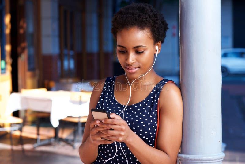 Jonge vrouw die aan muziek met oortelefoons luisteren en slimme telefoon bekijken stock foto