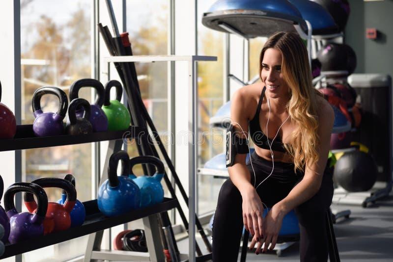 Jonge vrouw die aan muziek met smartphonezitting bij gymnastiek luisteren royalty-vrije stock foto's