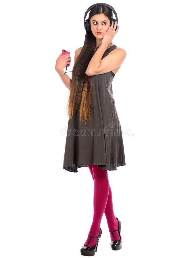 Jonge vrouw die aan muziek op mobiele telefoon luisteren stock afbeeldingen