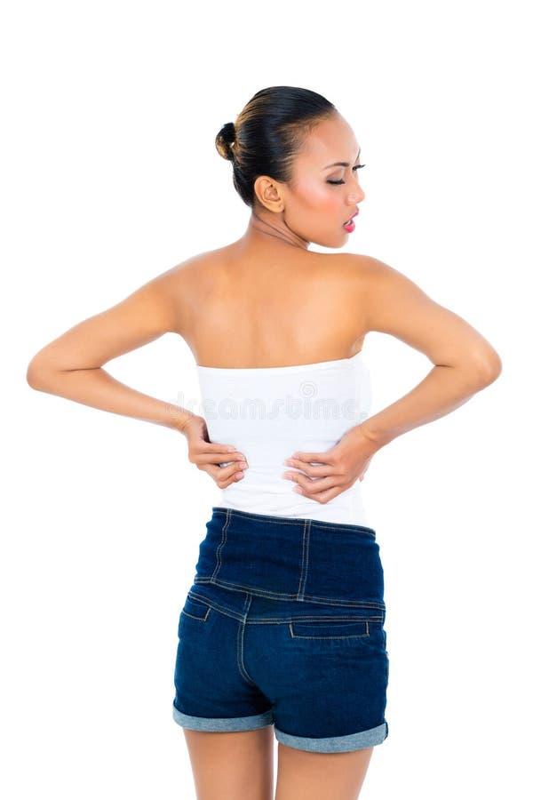 Jonge vrouw die aan rugpijn lijden stock foto